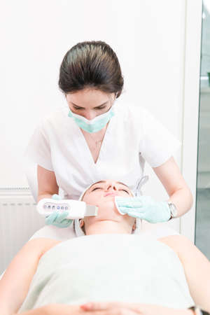 The female cosmetologist makes a procedure of ultrasonic cleaning face, close-up. Young woman in a beauty salon. Concept of cosmetology and professional skin care