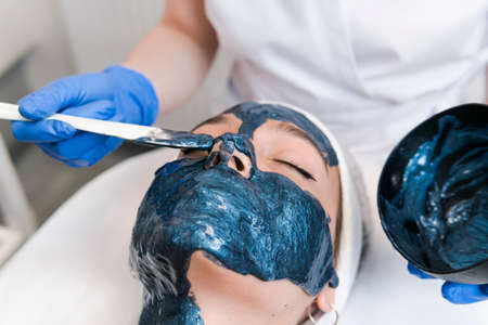 The young female client of cosmetic salon having a cleansing facial mask.