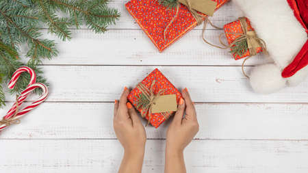 Female hands holding a gift box wrapping in the red paper, flat lay. Preparing for Christmas holidays. Top view of wooden table with fir tree branches and Santa Claus hat.