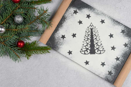 Silhouette of Christmas tree made of flour. Holiday background with copy space, tree branch, top view. Concept of Christmas dinner preparation and New Year eve.