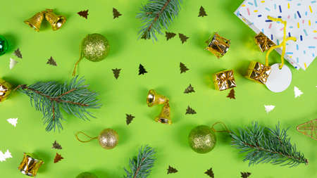 Fir tree branches and Christmas decorations on green background. Concept of New Year presents, festive and holiday shopping 免版税图像
