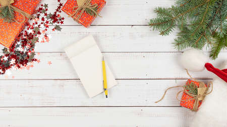 Flat lay of notebook on wooden background, Christmas decoration around. Concept of New Year, plans for the year and 2021 to do list Фото со стока