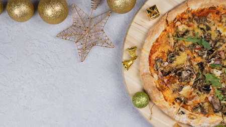 Flat lay of pizza on wooden salver, Christmas decorations around. Concept of discount and promotion in a pizzeria. Copy space, top view.