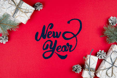 New Year lettering on red background, fir tree branches, silver cones and gift box around, flat lay. Concepts of greeting card. Top view.