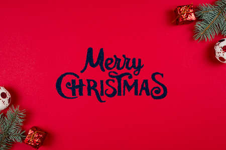 Merry Christmas lettering on red background, fir tree branches and New Years balls around, flat lay. Concepts of greeting card. Top view