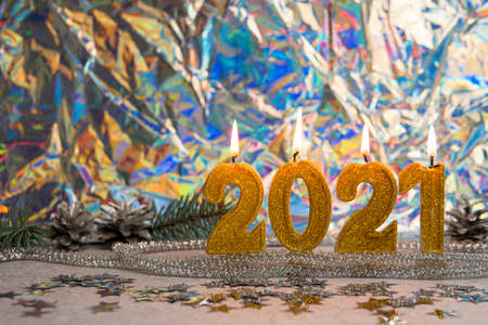 Burning golden candles 2021, close-up. Silver pine cones and branch are on the background. Concept of New Year and Christmas holidays. 免版税图像