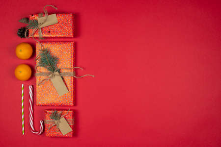 New Year and Christmas presents, handmade gift boxes wrapped with red paper and decorated fir tree branches, flat lay, red background. Copy space. Concepts of greeting card. Top view.