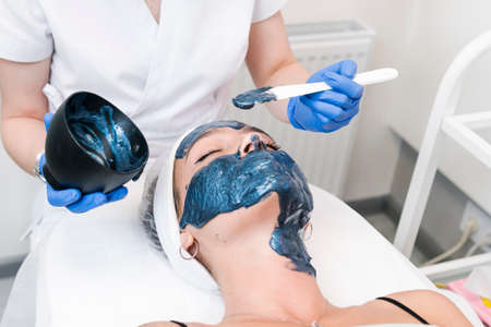 The young female client of cosmetic salon having a cleansing facial mask. The procedure of applying a peeling mask to the face. Concepts of skin care and beauty salon or clinic.