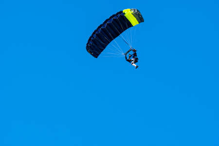 Tandem parachute jump. Silhouette of skydiver flying in blue clear sky. Concepts of extreme sport and adrenaline.