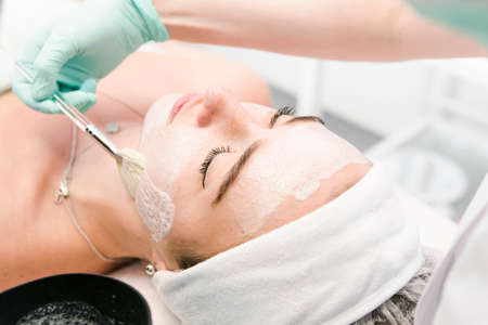 The young female client of cosmetic salon having a face cleaning procedure. The doctor cosmetologist cleaning skin. Concepts of skin care and beauty salon or clinic. Stockfoto