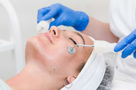 The young female client of cosmetic salon having microcurrent procedure on her face with special devices, close-up. Beautician using electrical impulses for facial procedures. Concepts of skin care product and beauty salon or clinic. Stockfoto