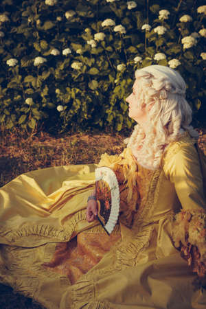 Portrait of blonde woman dressed in historical Baroque clothes with old fashion hairstyle, outdoors. Luxurious medieval dress