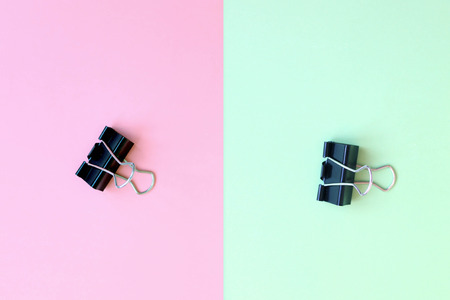 Black metal paper clip on pink and mint green double Phono background Stock Photo