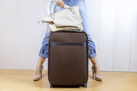 Young girl wearing jeans and high heels standing near the luggage bag and holding a handbag. Travel and relocation concept Stock Photo