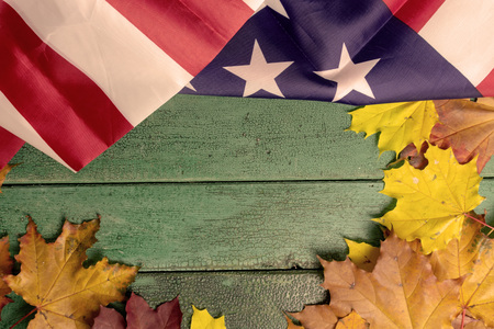 Green vintage wooden background covered with american flag and autumn leaves, copy space. Фото со стока