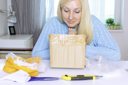 Excited blond woman sitting and opening a box, a parcel, objects on the table are in mess.