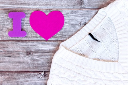 Sign i love made of letter and pink heart and white female sweater, pullover on vintage wooden background, flat lay. Stok Fotoğraf