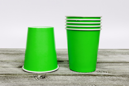 A stack of green take away disposable paper cups on wooden desk with white background. Stock Photo