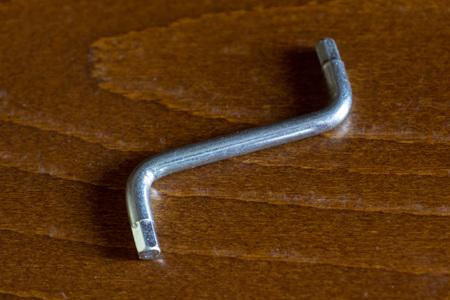 Allen key-hex wrench on brown wooden background.