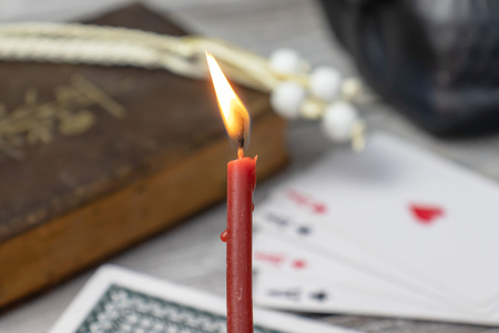 Burning church red candle in focus, blurred old holy bible, black skull and cards on wooden table. Misticism and fortune telling, future prediction concept.