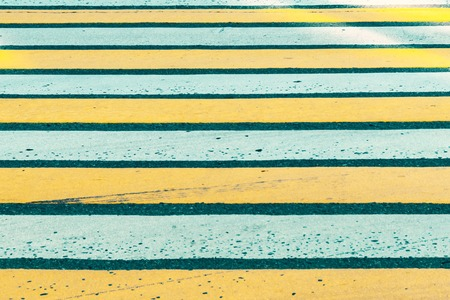 White and yellow pedestrian zebra crossing close up.