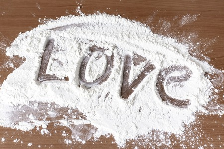 Sign love made of flour on wooden table, cooking with love concept.