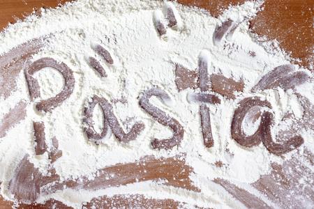 La palabra pasta escrita en la harina. Foto de archivo