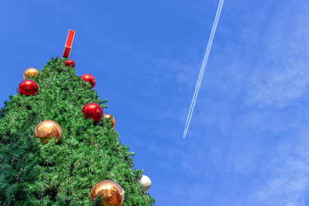 A giant christmas tree against blue sky with copy space.
