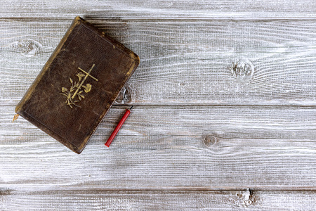 Catholic bible and red church nonflammable candle on wooden background with copy space. Stok Fotoğraf
