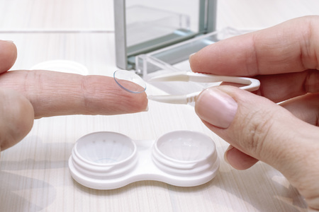 Cropped female hands taking contact lenses out of a container.