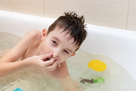 An eight year old boy sitting in bath and pinch the nose ready to dive.