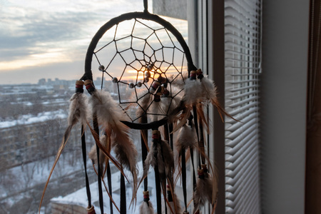 Handmade dreamcatcher hanging by the window in sunrise twilight. Urban city landscape on dackground. Black silhouette of traditional magic amulet for dream protection and bad spirits in the morning. Stock Photo