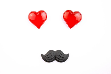 A funny face made of red hearts and plastic moustache on white background.