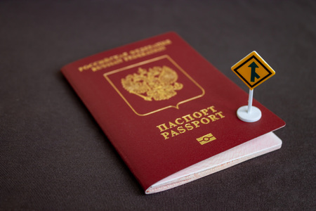 Russian international passport with a yellow arrow road sign - migration concept.
