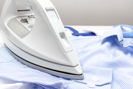 White modern electrical iron close up and blue shirts on the table - ironing, laundry and housework concept.