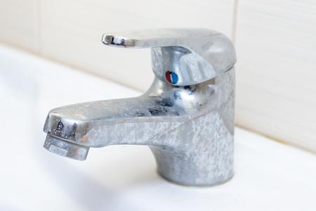 Schmutziger Wasserhahn mit Kalkablagerungen, verkalkter Wasserhahn mit Kalkablagerungen am Waschbecken im Badezimmer. Standard-Bild