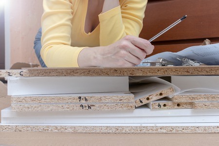 Woman sitting on the floor at home and assembling furniture using hand tools.