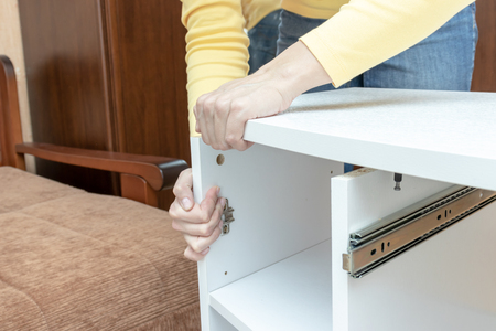 Woman mounting new white furniture, she putting a tabletop on a new half assembled dressing table. Stok Fotoğraf