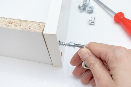 Close up view of a person assembling new white drawer using a screwdriver, tighten a screw with a hex allen key.