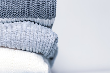Stack of cozy comfortable homely clean washed knitted sweaters in pastel colors, laundry and washing clothes concept with copy space.