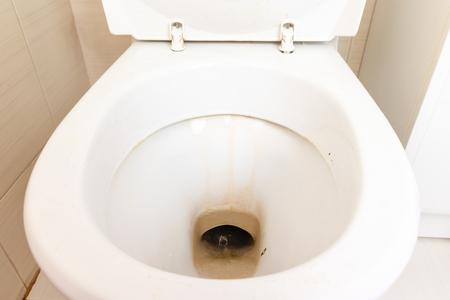 Schmutzige unhygienische Toilettenschüssel mit Kalkflecken auf der öffentlichen Toilette aus nächster Nähe.