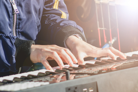 Pianist play the keys of the electronic synth at the outdoor performance. 写真素材