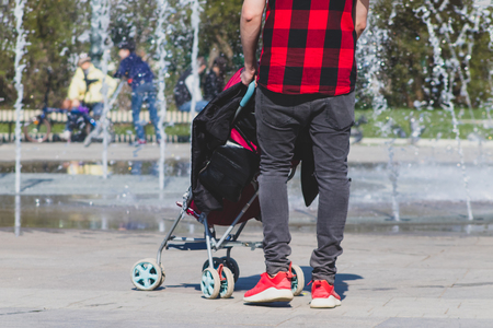 Lonely single father hipster in checkered red and black shirt with a stroller walking in the city park. 版權商用圖片