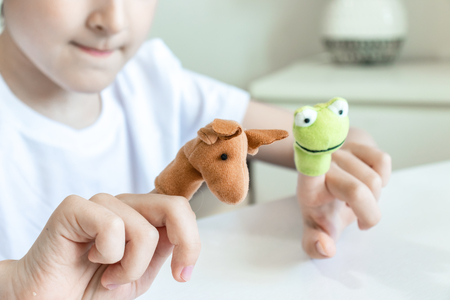 A caucasian boy playing finger puppets, toys, dolls - figures of animals, heroes of the puppet theatre put on fingers of human hand. Banco de Imagens