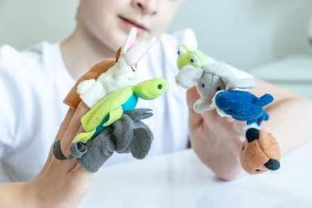 A caucasian boy playing different roles by using finger puppets, toys for expressing his emotions, agression, fear and freandship as a part of psychotherapy. Standard-Bild