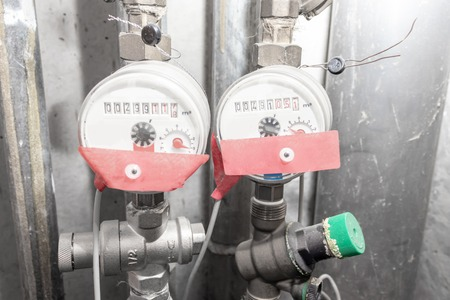 Water meters, counters of hot and cold water in bathroom service room at home.