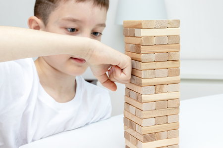 A preteen caucasian boy punching wooden block tower game with his arm.