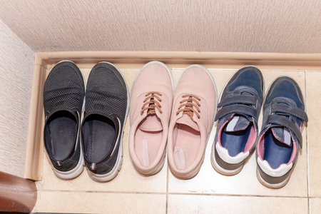 Three pairs of casual shoes - boots, sneakers, running shoes in the hallway.