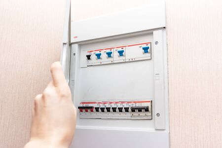 Moscow, Russia - May 07, 2019: Hand opening electrical shield with automatic switches of electricity in the house - electricity control panel with circuit breakers. Stockfoto - 133072443
