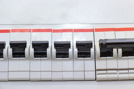 Row of automatic switches of electricity in the electrical shield in the house close up.